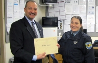 Officer Jenkins receives her commendation from Jeff Edmiston.